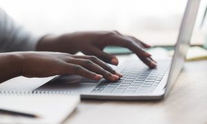 Closeup of unrecognizable afro woman typing on laptop keyboard while working in office, panorama