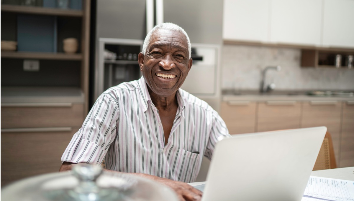 Portrait of a senior man using laptop in the kitchen table